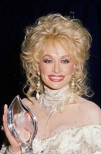 Dolly Parton, one of the richest artists of all time, holding a People's Choice Awards in 1988.